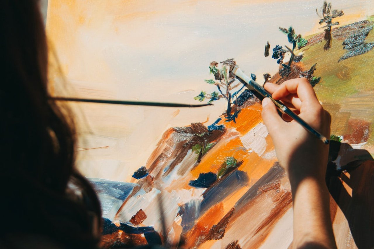 A hand holding a paintbrush on a painting.