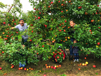 Family picking apples in fall